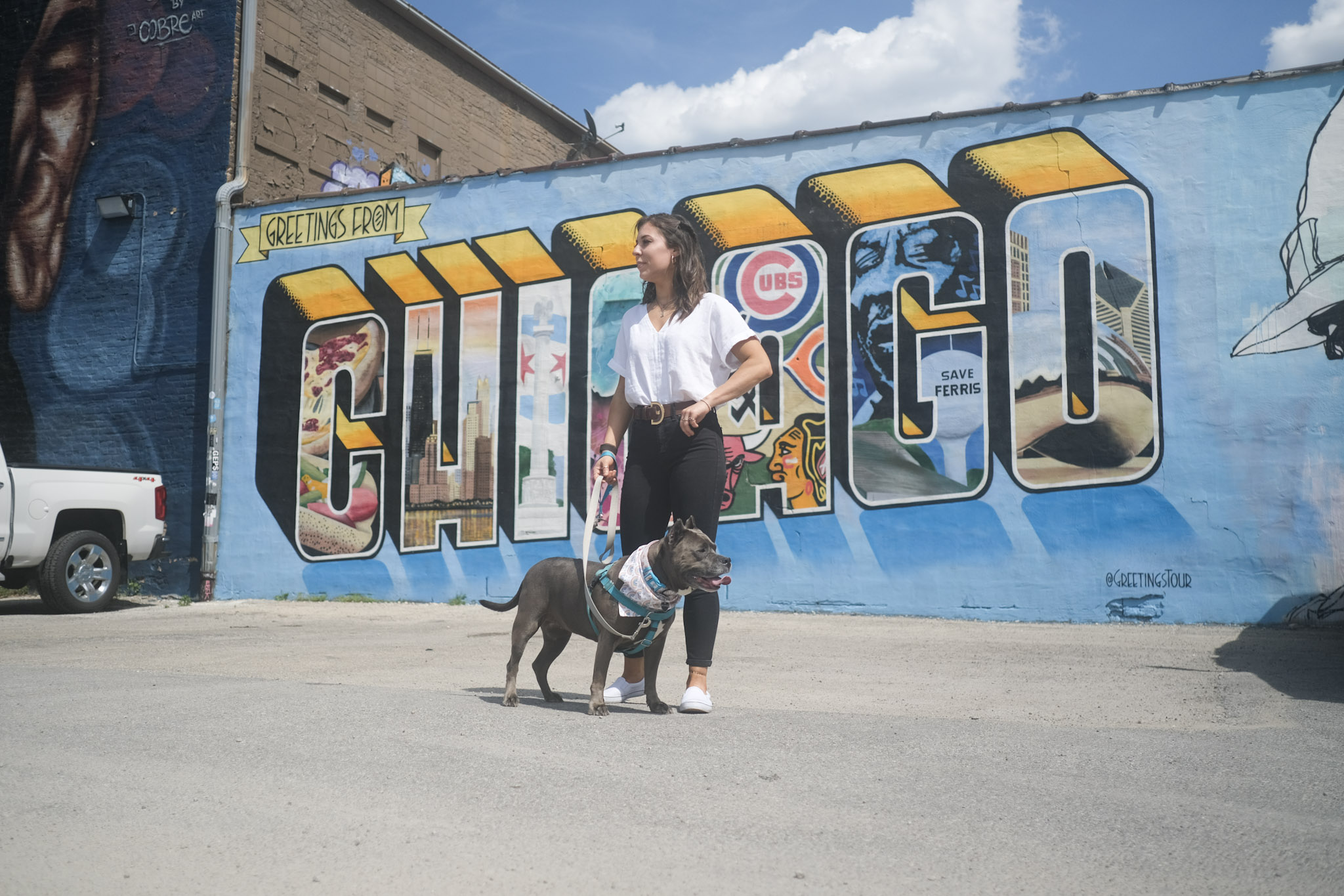 Woman stands with her dog in front of a mural